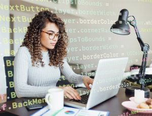 Woman sitting at desk typing code on laptop